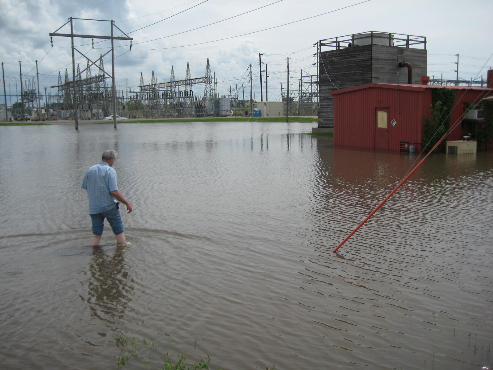 Dave Reese - NWS Des Moines Electronics Systems Analysts treads flooded water from the Iowa River at Marshalltown. The small building at the right is where the Marshalltown NOAA Weather Radio Transmitter is located. There was already about a foot of flood water into the building. Photo taken June 9, 2008 by Ken Podrazik.